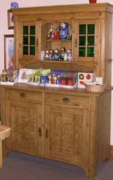 An original restored pine dresser with leaded glazing and carved panel lower doors