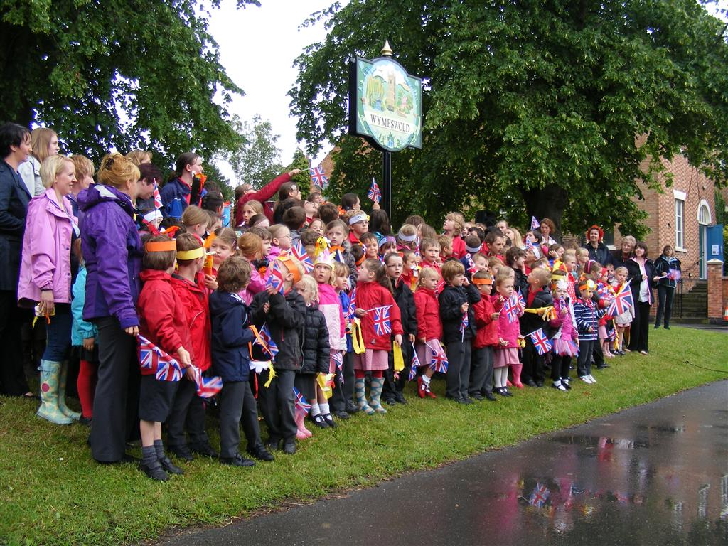Children and staff of Wymeswold School gather around the sign